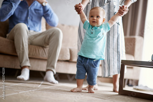 Happy family -Smiling baby learning walking with mother, child enjoys the first steps.