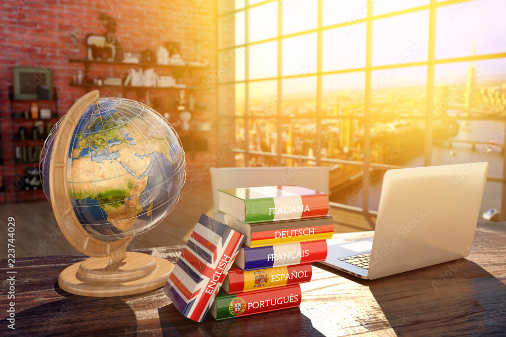 Fototapeta Languages learning and translate, communication and travel concept, books with covers in colors of flags of Europe countries, laptop and globe on a table in a modern interior