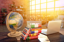 Languages Learning And Translate, Communication And Travel Concept, Books With Covers In Colors Of Flags Of Europe Countries, Laptop And Globe On A Table In A Modern Interior