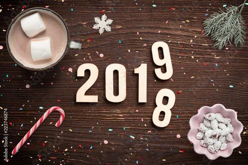 Jahreswechsel zwischen 2018 und 2019 mit winterlicher Dekoration auf rustikalem Holzuntergrund