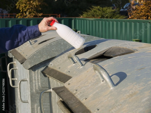 Fotografie, Obraz  Man throws a plastic bottle into a garbage can