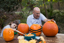 A Girl And Her Father Making A Jack-o-lantern From A Pumpkin.
