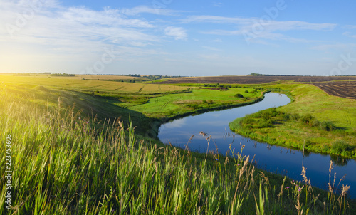 Beautiful view of river curve,green and yellow fields illuminated by the warm light of rising sun.