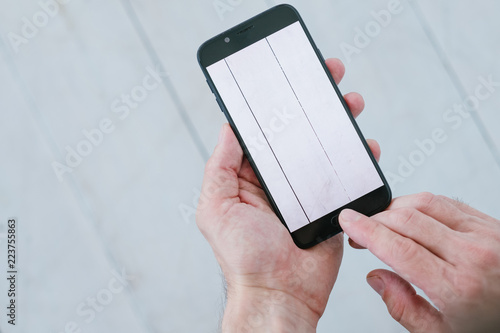Fototapety, obrazy: blogger taking photos of white wooden background. social media influencer creating content for channel. hands holding smartphone. mobile photography concept