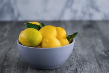 Fresh Ripe Lemons In Blue Bowl On Gray Wooden Table.