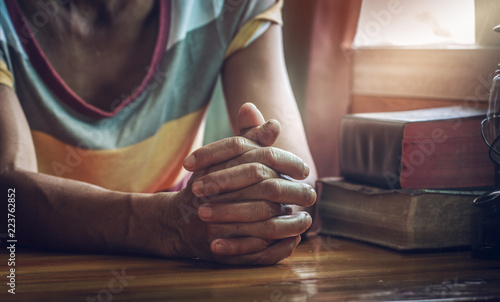 Close Up Hands Of Old Woman While Praying On Wooden Table With Bible