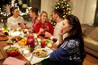 holidays, communication and celebration concept - happy young woman calling on smartphone and having christmas dinner with friends at home
