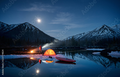 View of camp life in a mountain terrain. Lake shore with canoe Wallpaper Mural
