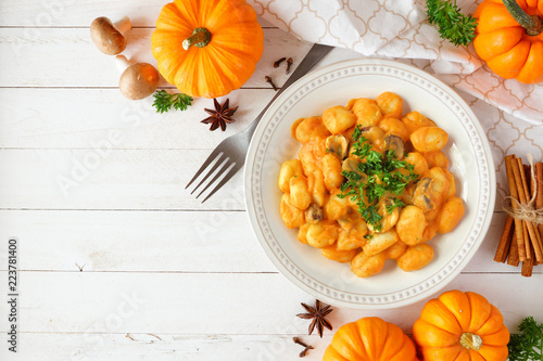Gnocchi with a pumpkin, mushroom cream sauce. Autumn meal. Top view table scene on a white wood background with copy space.