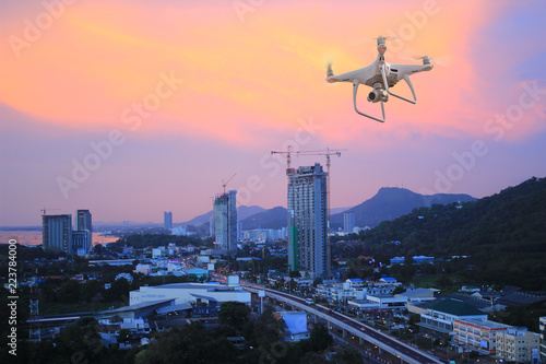UAV drone copter flying with digital camera.Drone with high resolution digital camera. Flying camera take a photo and video.The drone with professional camera take pictures of the cityscape