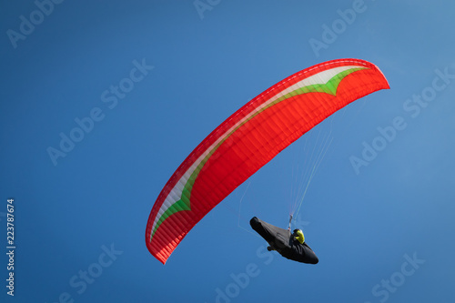 Foto op Canvas Luchtsport Close up, Guy flying on the clearly blue sky with a red paraglider,extreme activity