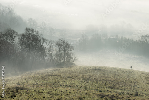 Fotobehang Wit Stunning foggy English rural landscape at sunrise in Winter with layers rolling through the fields