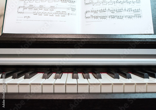 Staande foto Muziekwinkel 2018.09.18, Moscow, Russia. An open book of sheet music on the piano. A composition of the sheet music and the piano keyboard. Elements of interior of the music classroom.