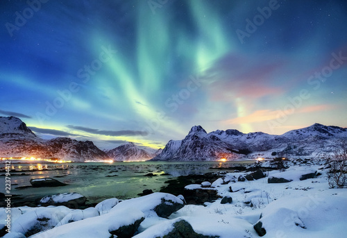 Foto auf Gartenposter Nordlicht Aurora borealis on the Lofoten islands, Norway. Green northern lights above mountains. Night sky with polar lights. Night winter landscape with aurora and reflection on the water surface.