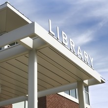 White Library Sign With Blue Slightly Cloudy Sky In The Background