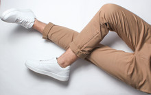 Fragment Of Male Legs In Beige Trousers And White Sneakers Sits On A White Background. Top View. Relaxation.