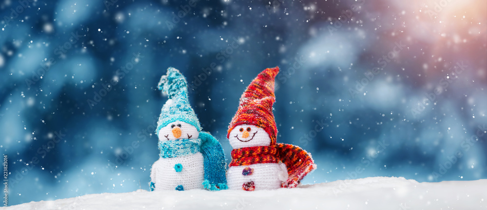 Fototapety, obrazy: little knitted snowmans on soft snow on blue background