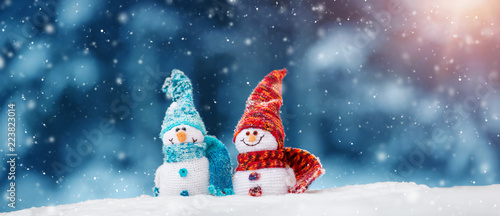 Fotomural  little knitted snowmans on soft snow on blue background