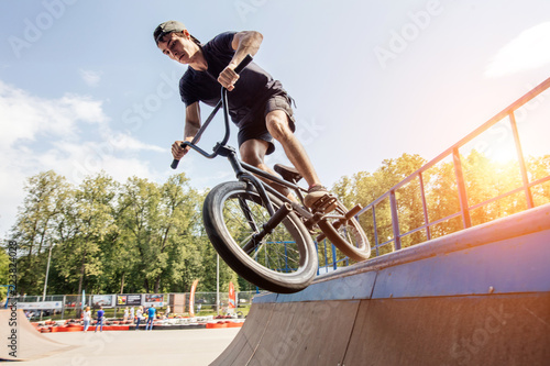 boy doing jump trick with his BMX at skatepark