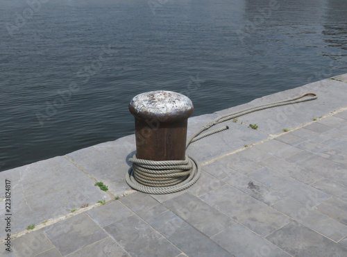 Fotografía  pier or jetty with a rope on a bollard in the harbor of Antwerp