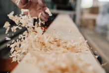 Hand Sweeps Sawdust From A Wooden Beam