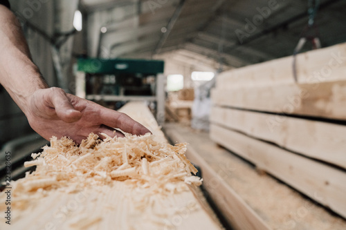 Fotografie, Obraz  hand sweeps sawdust from a wooden beam