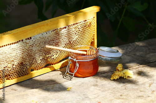 jar of fresh honey in a glass jar on an old table on a apiary Canvas Print