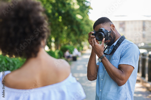 African-american photographer taking photos of beautiful woman Wallpaper Mural