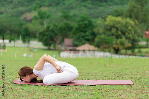 Beautiful Attractive Asian Woman Practice Yoga Mudrasana Pose Lying On Yoga Mat With Green Grass For Yoga Meditation Feeling So Relax And Comfortable Healthcare Concept Buy This Stock Photo And Explore Similar