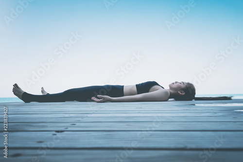 Beautiful Attractive Asian woman relaxing in yoga Savasana or dead body pose to meditation warm up her muscle on beach in Maldives with seaside,Feeling so comfortable and relax in holiday,Vintage Tone