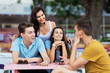 A company of good-looking friends is laughing, socialising and sitting at the table in the nice summer cafe. Entertainment, having good time. Friendship.