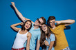 Four good-looking friends are laughing while standing in front of the blue wall having confident and happy looks. Entertainment, having good time. Friendship, relationship.