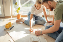 Portrait Of Happy Caucsian Couple Planning New House Design Looking At Paper