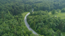 AERIAL: Flying Above Cars Driving Down Road Winding Through Dark Green Forest.