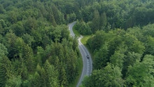 AERIAL: Flying Behind A Single Black Car Driving Down The Scenic Country Road.
