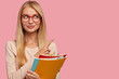 Leinwanddruck Bild - Cheerful pleasant looking European woman with light hair, wears glasses, points with index finger at upper right corner, shows free space for your advertisement, carries textbooks for studying
