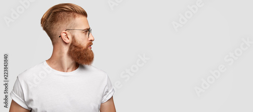 Sideways shot of brutal man with ginger thick beard, trendy hairstyle, looks tho Fototapet