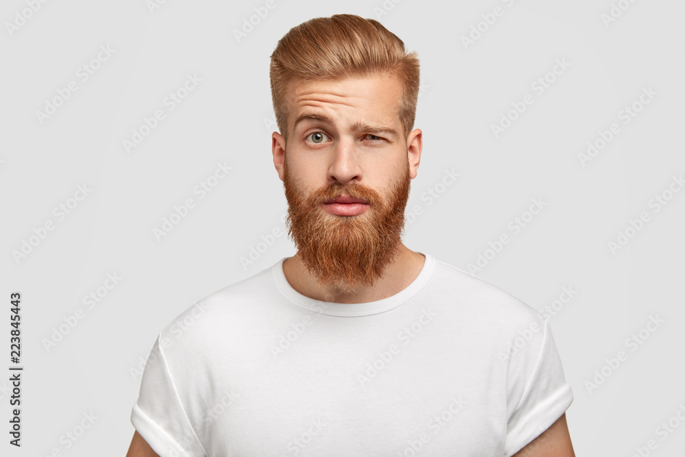 Fototapeta Bewildered man with thick ginger beard, raises eyebrows, reacts on fake news from friend, looks directly at camera, dressed in casual t shirt, isolated over white background. Facial expressions