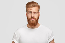 Bewildered Man With Thick Ginger Beard, Raises Eyebrows, Reacts On Fake News From Friend, Looks Directly At Camera, Dressed In Casual T Shirt, Isolated Over White Background. Facial Expressions
