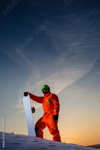 Snowboarder on the top of the ski slope at the background of beautiful sunset