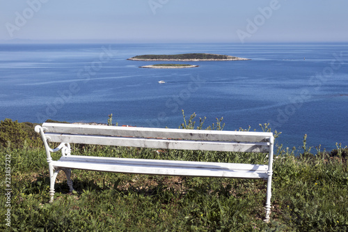 Fotografie, Obraz  White bench on green hill with view at blue Adriatic sea on island Vis in Croati