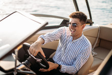 Cheerful Professional Sales Manager Sells Luxury Motor Boats And Yachts, Holding The Steering Wheel In Hands And Demonstrating Perfect Boat S Features