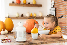 Cute Little Girl Eating Pumpkin Soup In Halloween Decorated Dinning Room. Autumn Season Food Lifestyle Background.