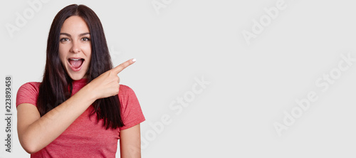 Horizontal shot of surprised brunette woman with dark hair, dressed in pink t shirt, points with index finger asie, shows free space for your promotion, notices something unbelievable. Look there!