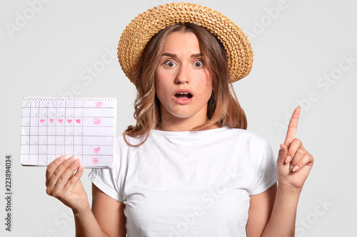 Fotografie, Obraz  Shocked European woman with terrified expression, raises index finger, wears straw hat and casual t shirt, holds periods calendar, isolated over white background