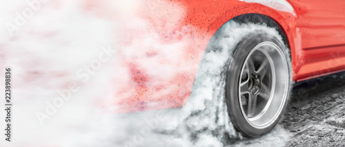 Photo Drag racing car burns rubber off its tires in preparation for the race
