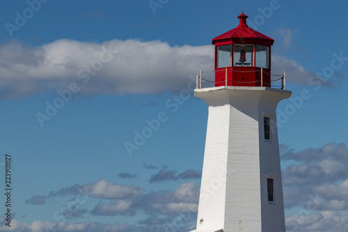 Peggy's Cove Lighthouse closeup, summer, light clouds, blue sky.