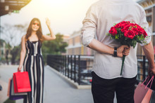 Man Holding A Red Flower Behind His Back To Surprise Your Lover.