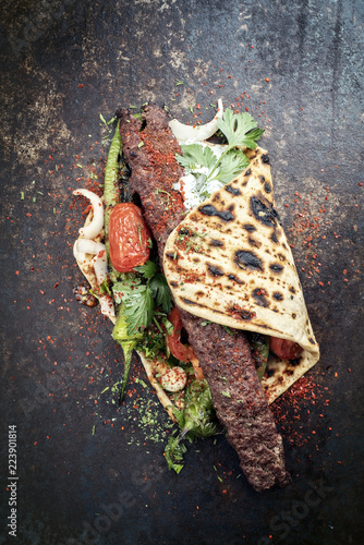 Traditionelles Adana Kebap auf einem Grillspieß mit Tomaten und  Jogurt auf einem Fladenbrot