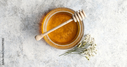 Fotografia From above view of bowl full of yellow honey with spindle decorated with herb on